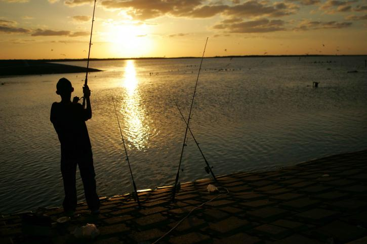 young-man-stands-fishing-at-sunset-725x483